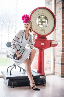 woman-in-pink-hat-sitting-on-chair-on-giant-scales