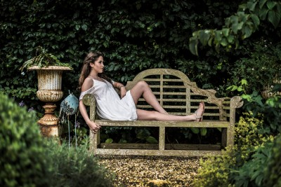 woman-laying-on-bench-in-white-dress