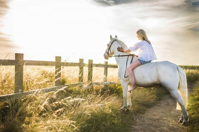 woman-on-white-horse-in-field
