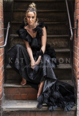 woman-in-black-dress-sitting-on-stairs