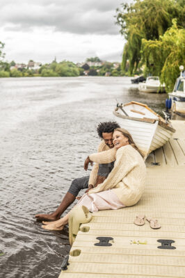 man-and-woman-sitting-by-river-bank